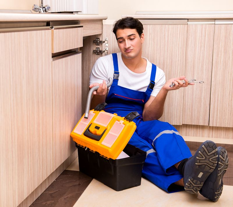 an amateur plumber sitting on the floor